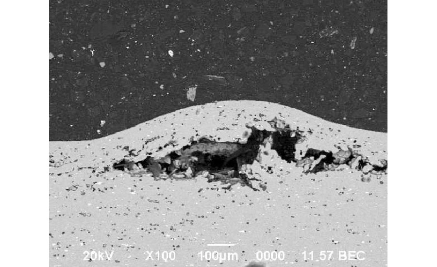 Backscatter electron image of the blistered surface of the part showing a large blister with subsurface porosity