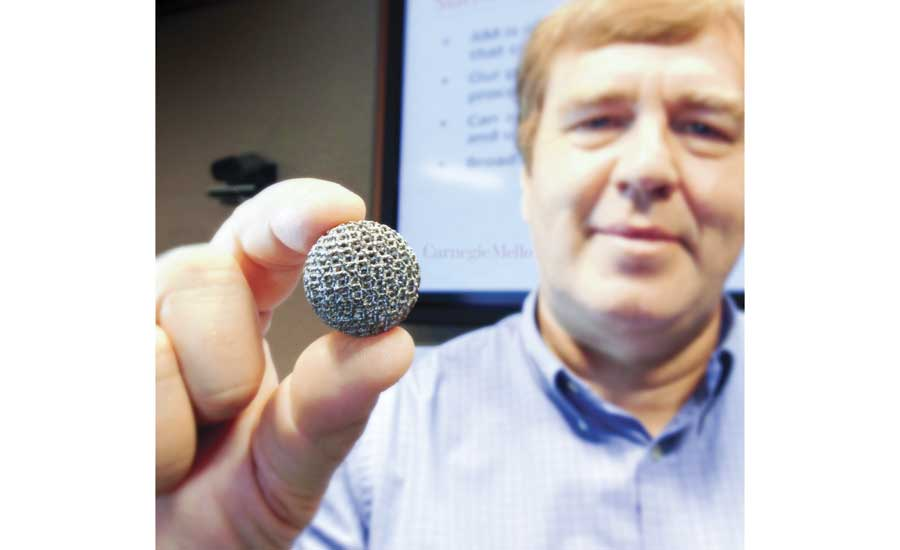 Jack Beuth holds a 3D-printed sphere that was created in his undergraduate class