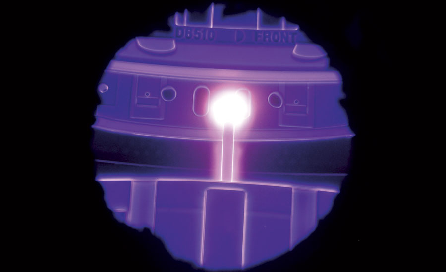 Two large-size stamping dies during plasma nitriding viewed through the port window