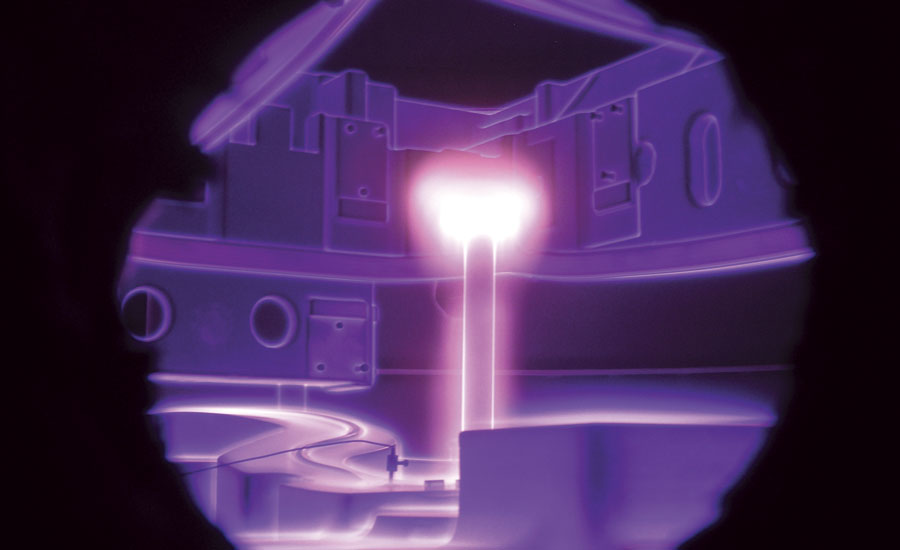 Two dies during plasma nitriding viewed through the port window with intense glow around the central anode